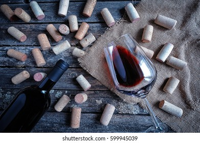 Bottle and glass of red wine on rustic wooden background with burlap