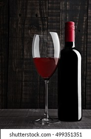 Bottle and glass of red wine with reflection on wooden background