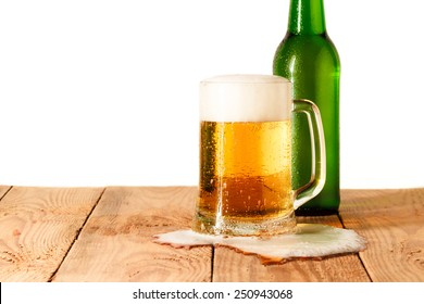 Bottle, glass and spilled beer on old wooden table. Isolated on white background