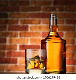 Bottle and glass of whiskey with ice on brick wall background