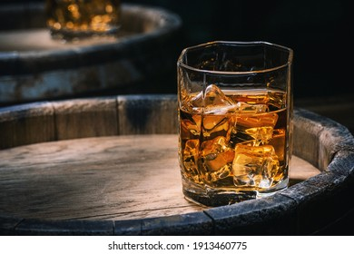Bottle and glass of whiskey with ice on a wooden background. Glass of Scotch whiskey and ice sits on top of a rustic whiskey barrel. Whiskey with ice.