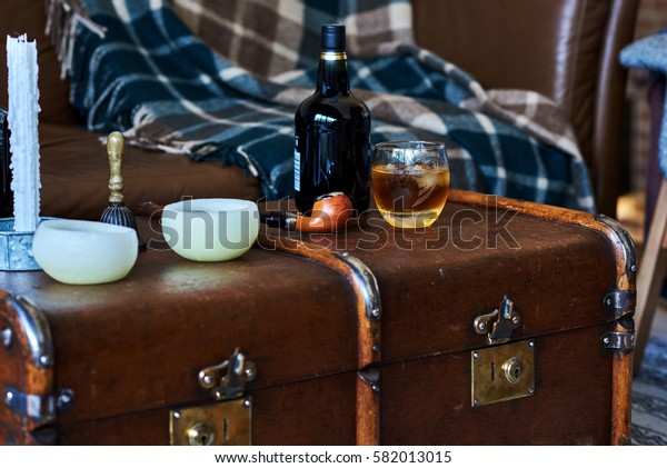 Bottle and glass of whiskey with ice on a wooden old suitcase.