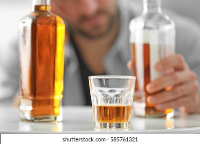 Bottle and glass of whisky with blurred man on background
