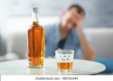Bottle and glass of whisky on white table
