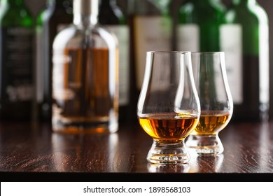 Bottle and glass of whisky spirit brandy on dark brown background