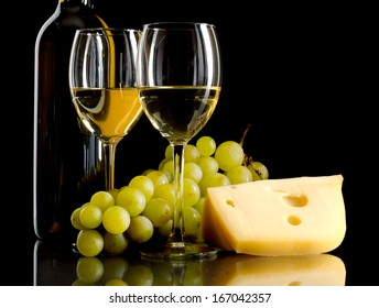 A bottle and a glass of white wine, a bunch of white grapes and cheese on black background