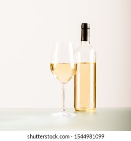 Bottle and a glass of white wine on a white background.