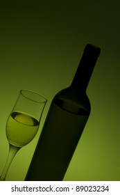 bottle and glass with white wine on green background