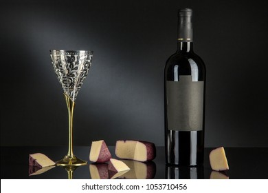 bottle with a glass, wine and cheese, a bottle of wine and cheese