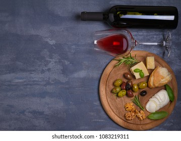 Bottle and glass of wine with cheese, olives, bread, nuts and rosemary on dark background. Wine and food concept, banner. overhead, horizontal