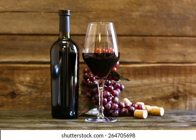 Bottle and glass of wine with grape on wooden background