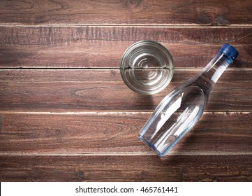Bottle and Glasses of water on a wooden table,top view