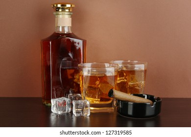Bottle and Glasses of whiskey and cigar on brown background