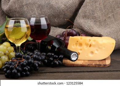 bottle and glasses of wine, cheese and grapes on grey background