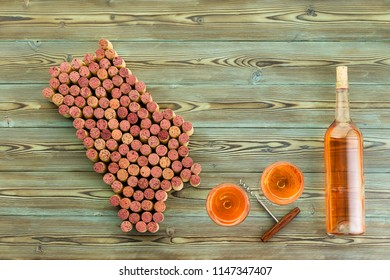 Bottle and glasses of wine and corkscrew with Napa Valley map formed of used stained red wine corks on rustic wood with copy space in a viticulture concept