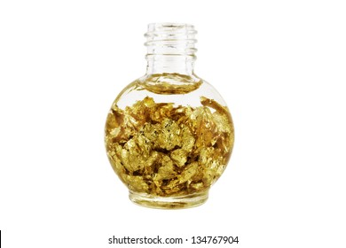 Bottle of gold flakes in front of white background.