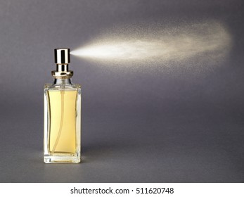 Bottle of golden colored perfume with spray jet on gray background