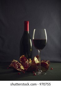 A bottle of good french wine, a piece of stemware and a pomegranate plus a couple of draperies.
