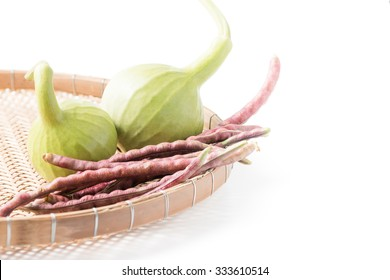 bottle gourd fruit and purple cowpea in basket isolated on white