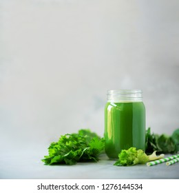 Bottle of green celery smoothie on grey concrete background with copy space. Square crop. Fresh juice for detox. Vegan, alkaline healthy diet concept.