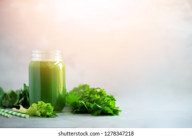 Bottle of green celery smoothie on grey concrete background. Banner with copy space. Square crop. Fresh juice for detox. Vegan, alkaline healthy diet concept.