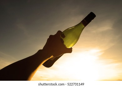 Bottle in hand with sunset