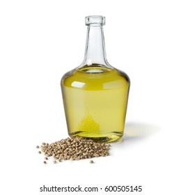 Bottle with hemp oil and unshelled hemp seed on white background