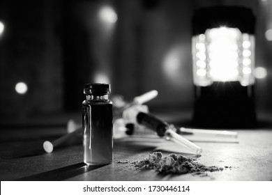 Bottle of heroin and narcotic syringes. In syringes and vials, the liquid is yellow, blue, and purple. cocaine and other drugs on old plywood in a dark room. Illuminated by cold and warm light.