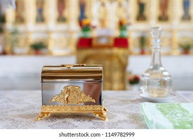 Bottle of holy water is out of focus and a box with tassels for anointing at christianity