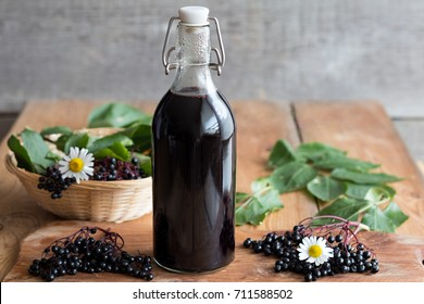 A bottle of homemade elderberry syrup on a wooden table, with fresh elderberries in the background