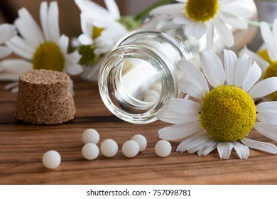 A bottle of homeopathic globules with chamomile flowers on a table