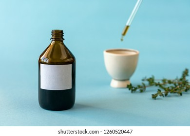 A bottle of homeopathic oil with a drip. Close-up of glass bottle with clean paper and dropper with healing homeopathic drops on blue. Homeopathic drops in a glass bottle, pipette, medicine
