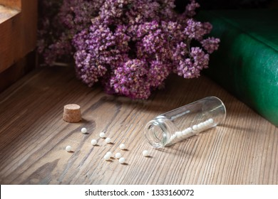 A bottle of homeopathic pills with dried herbs and a book