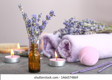 Bottle with lavender flowers on grey table