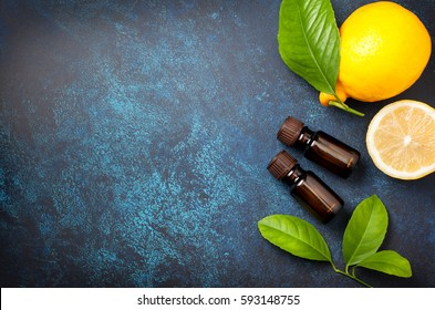 bottle with lemon essential oil, fresh lemon on a blue background