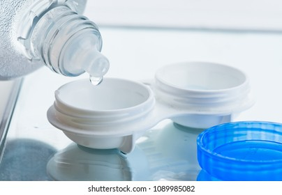 Bottle with lens solution and case on table