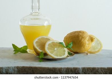 Bottle of limoncello and lemons of Sorrento decorated with mint on the light background