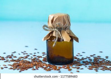 A bottle of linseed oil and flaxseed on a blue background. Care for the stomach and intestines