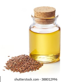 Bottle of linseed oil and linseeds isolated on white background