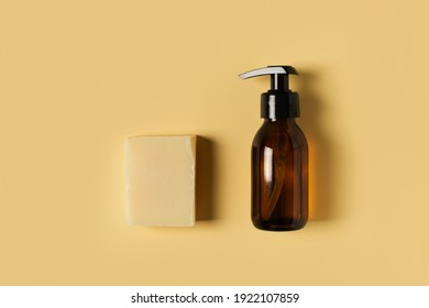 Bottle of liquid and bar soap on yellow background, copy space, flat lay, top view