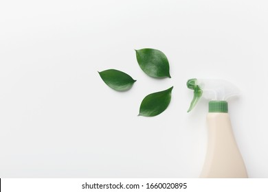 Bottle for liquid detergent, cleaning agent, with natural plant extract and green leaves on white background, copy space