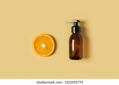 Bottle of liquid soap with orange on yellow background, copy space, flat lay, top view