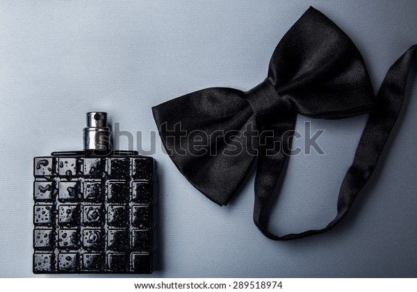 Bottle of male perfume and black bow tie