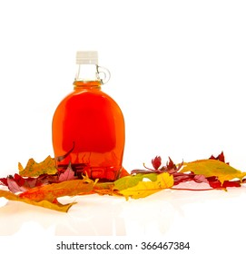 Bottle of maple syrup with leaves from a maple tree.