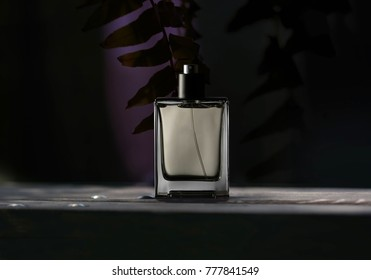 A bottle of men's perfume on a dark background.