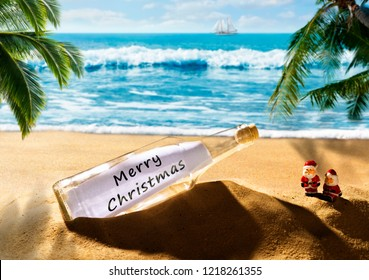 Bottle with the message Merry Christmas on a beautiful tropical beach
