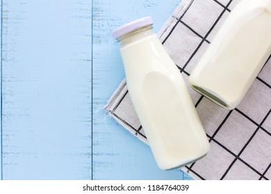 Bottle of milk on blue wooden background.
