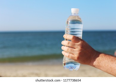 bottle of mineral water in hand with blue sea and beach background