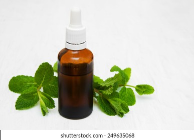 Bottle of mint oil and fresh mint  on a old wooden background