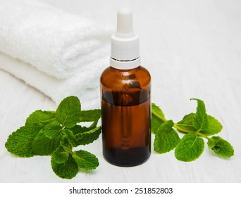Bottle of mint oil and fresh mint with white towel on a old wooden background